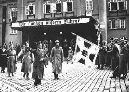 """<p>Adolf Hitler in Brno shortly after German troops occupied <a href=""""/narrative/7295"""">Czechoslovakia</a>. The sign reads, """"We thank our Führer."""" Brno, Czechoslovakia, March 17, 1939.</p>"""