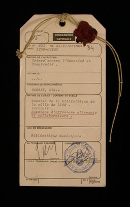 <p>Evidence tag from the trial of Klaus Barbie in Lyon, France. This standard police form lists Barbie's infractions as crimes against humanity and complicity, concepts defined at the International Military Tribunal at Nuremberg decades earlier. The line in which the victims' names would be recorded is left blank. February 25, 1983.</p>