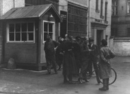 "<p>Police search a messenger at the entrance to the building where <em>Vorwaerts</em>, a Social-Democratic Party newspaper, was published. The building was subsequently occupied during the suppression of the political left wing in Germany that was carried out in response to the <a href=""/narrative/11461/en"">Reichstag Fire</a>. Berlin, Germany, March 3–4, 1933.</p>"