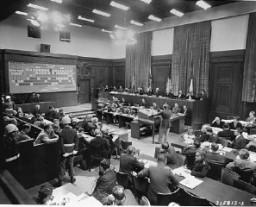 <p>الرائد الأمريكي فرانك ب. واليس (يقف في الوسط), وهو عضو من الموظفين القانونيين للمحاكمة, يعرض ملف الاتهام للمحكمة العسكرية الدولية بنورنبرغ. يظهر رسم بياني (أعلى اليسار) دور المدعين عليهم (أسفل اليسار) في المخطط التنظيمي للحزب النازي. على اليمين هناك محامو جهة الادعاء للدول الأربعة. 22 نوفمبر 1945.</p>