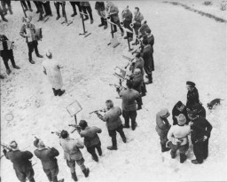 <p>Members of the orchestra at the Janowska concentration camp perform while standing in a circle around the conductor in the <em>Appelplatz</em> [roll call area]. Pictured at the right, in the light uniform, is camp commandant Warzok Franz.</p>