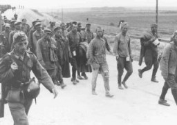 """<p>German soldiers guard Soviet prisoners of war marching to camps. Soviet Union, 1941.</p> <p>Second only to the Jews, Soviet prisoners of war were the largest group of victims of<a href=""""https://encyclopedia.ushmm.org/narrative/10962/en"""">Nazi racial policy</a>.</p>"""