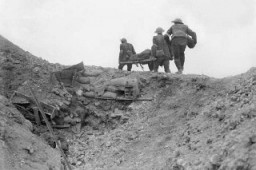 Stretcher bearers carry a wounded soldier during the Battle of the Somme. [LCID: 2453747]