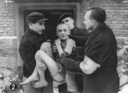 Soon after liberation, an emaciated child survivor is carried out of camp barracks by Soviet first-aid workers. [LCID: 63300]