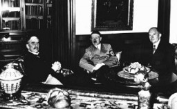 """<p>British prime minister <a href=""""/narrative/11821"""">Neville Chamberlain</a> (left), German chancellor Adolf Hitler (center), and French premier Edouard Daladier (right) meet in Munich to determine the fate of <a href=""""/narrative/7295"""">Czechoslovakia</a>. Germany, September 30, 1938.</p>"""