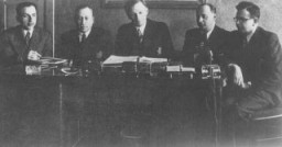 "<p>A meeting of the <a href=""/narrative/3182/en"">Kovno</a> ghetto <a href=""/narrative/4696/en"">Jewish council</a>. Chairman Elchanan Elkes sits at the center. Kovno, Lithuania, 1943.</p>"