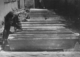 "<p>A woman mourns by the coffins of Jews who died in the <a href=""/narrative/11504"">Kielce</a> pogrom. Poland, July 6, 1946.</p>"