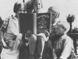 """<p>독일 어린이들이 DER GIFTPILZ (""""독버섯"""")이라는 제목의 반 유태주의 선전 책자를 읽고 있다. 좌측의 소녀 역시 같은 종류의 책을 읽고 있는데 이 책의 제목을 번역하면 """"여우를 믿지 마라""""는 것이다. 독일,  1938년 경.</p>"""