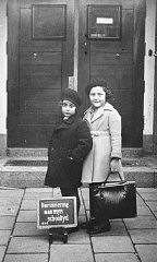 Portrait of Hetty d'Ancona Deleeuwe (left) and her best friend, Judith Konyn, standing at the entrance to their school on their first day of classes.