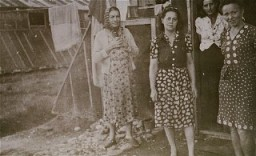 """<p>Women prisoners standing in front of barracks at the <a href=""""/narrative/4842/en"""">Gurs</a> camp. Gurs, France, ca. 1943.</p>"""