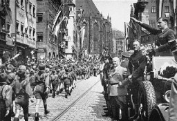 "<p>Members of the Hitler Youth march before their leader, <a href=""/narrative/9908"">Baldur von Schirach</a> (at right, saluting), and other Nazi officials including <a href=""/narrative/10706"">Julius Streicher</a>. Nuremberg, Germany, 1933.</p>"