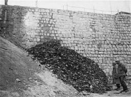 Dopo la liberazione del campo di concentramento di Flossenbürg, due soldati di fanteria americani esaminano una pila di scarpe appartenute alle vittime del campo.