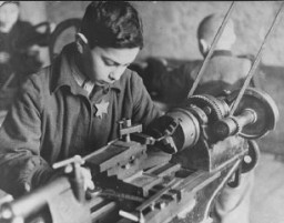 <p>Yakob Vizgordiski works at a machine in a ghetto factory. Kovno, Lithuania, between 1941 and 1943.</p>