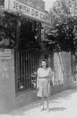 """<p>This photograph shows Dina Sarna in front of a sign saying """"Jewish DP Camp""""in the <a href=""""/narrative/11688/en"""">Bad Reichenhall</a> camp for Jewish displaced persons. Bad Reichenhall, Germany, 1947.</p>"""