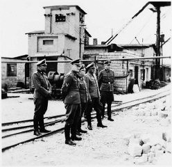 <p>Commandant Arthur Roedl (center) and SS officers visit the Gross-Rosen concentration camp's quarry. Gross-Rosen, Germany, 1941.</p>