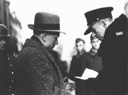 "<p>A Polish policeman checks the papers of a Jewish resident of the <a href=""/narrative/2014"">Warsaw</a> ghetto. Warsaw, Poland, February 1941.</p>"