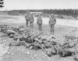 "<p>US soldiers view bodies of victims of <a href=""/narrative/8071/en"">Kaufering</a>, a network of subsidiary camps of the Dachau concentration camp. Landsberg-Kaufering, Germany, April 30, 1945.</p>"