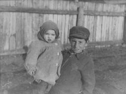 "<p>A young boy holding his younger brother in the <a href=""/narrative/3182"">Kovno</a> ghetto. Older children frequently cared for younger siblings in the ghetto. Photographed by <a href=""/narrative/11692"">George Kadish</a>. Kovno, Lithuania, 1941.</p>"