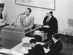 "<p>Henryk Ross testifies during <a href=""/narrative/3359/en"">Adolf Eichmann's trial</a>. In addition to official duties as a photographer in the Department of Statistics in the <a href=""/narrative/2152/en"">Lodz</a> ghetto, Ross secretly photographed scenes in the ghetto. To Ross' right is chief prosecutor Gideon Hausner, who holds some of Ross' photographs submitted as evidence. Jerusalem, Israel, May 2, 1961.</p>"