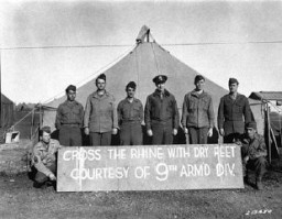 """<p>The commanding general of the 9th Armored Division (third from right), and members of the division who won the Distinguished Service Cross pose with the sign placed on the Ludendorff Bridge after its capture. <a href=""""/narrative/8129"""">US Army Signal Corps</a> photograph taken by W. Spangle on September 18, 1945, several months after the bridge was captured.</p>"""