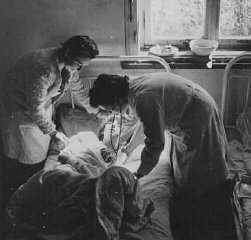 "<p>Soon after <a href=""/narrative/8176"">liberation</a>, a camp survivor receives medical care. Bergen-Belsen, Germany, after April 15, 1945.</p>"
