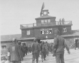 "<p>American soldiers and liberated prisoners at the main entrance of the <a href=""/narrative/3956/en"">Buchenwald</a> concentration camp. Germany, May 1945.</p>"