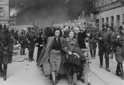 "<p>German soldiers lead Jews captured during the <a href=""/narrative/3636/en"">Warsaw ghetto uprising</a> to the assembly point for deportation. Poland, May 1943.</p>"