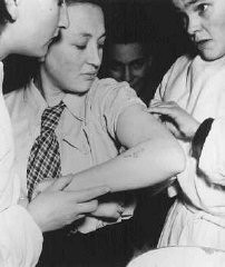 """<p>A former concentration camp prisoner receives care from a mobile medical unit of the <a href=""""/narrative/7232/en"""">United Nations Relief and Rehabilitation Administration</a>. Photograph taken at the<a href=""""/narrative/9359/en"""">Bergen-Belsen displaced persons camp</a>. Germany, May 1946.</p>"""
