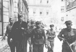 <p>Amon Goeth (front left), commandant of the Plaszow camp, under escort to the courthouse in Kraków for sentencing. He was sentenced to death at his postwar trial on war crimes charges. Kraków, Poland, August 1946.</p>