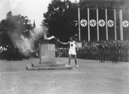 "<p>The last of the 3,000 runners who carried the Olympic torch from Greece lights the Olympic Flame in Berlin to start the 11th <a href=""/narrative/7139"">Summer Olympic Games</a>. Berlin, Germany, August 1936.</p>"