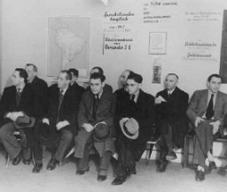 "<p>German Jews seeking to <a href=""/narrative/6473"">emigrate</a> wait in the office of the <em>Hilfsverein der Deutschen Juden</em> (Relief Organization of German Jews). On the wall is a map of South America and a sign about emigration to Palestine. <a href=""/narrative/5908"">Berlin</a>, Germany, 1935.</p>"