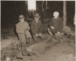 "<p>Three German mayors view the corpse of a prisoner burned alive in a barn by the SS while on a death march from Rottleberode, a subcamp of Dora-Mittelbau. <a href=""/narrative/8101"">Gardelegen</a>, Germany, April 18, 1945.</p>"