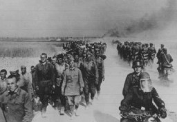 "<p>At left, a column of <a href=""/narrative/10135/en"">Soviet prisoners of war</a>, under German guard, marches away from the front. Place uncertain, July 1, 1941.</p>"