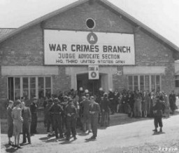 "<p>A crowd waits outside the American military court for the announcement of a verdict in the <a href=""/narrative/24610/en"">Malmedy</a> war crimes trial of SS soldiers accused of taking part in the massacre of American prisoners of war. Dachau, Germany, July 16, 1946.</p>"