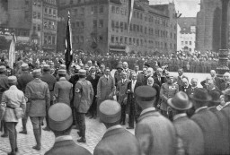 "<p><a href=""/narrative/312"">Adolf Hitler</a>, <a href=""/narrative/10706"">Julius Streicher</a>, and other dignitaries review passing <a href=""/narrative/61038"">Nazi Party</a> members at the <em>Deutscher Tag</em> (German Day) celebration in Nuremberg, September 02, 1923.</p>"