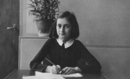 <p>Anne Frank, age twelve, at her school desk. Amsterdam, the Netherlands, 1941.</p>