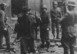 "<p>SS personnel capture two Jewish resistance fighters who were pulled from a bunker during the suppression of the <a href=""/narrative/3636/en"">Warsaw ghetto uprising</a>.  Warsaw, Poland, April 19-May 16, 1943.</p>"