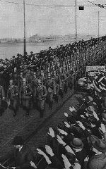 """<p>During the remilitarization of the Rhineland, German civilians salute German forces crossing the Rhine River in open violation of the <a href=""""/narrative/116/en"""">Treaty of Versailles</a>. Mainz, Germany, March 7, 1936.</p>"""