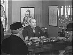 <p>German forces entered Warsaw in September 1939. The next month, they ordered the establishment of a Jewish council (Judenrat) in the city. They chose Adam Czerniakow, a member of Warsaw's old Jewish Community Council, to lead it. Here, for German newsreels, a German propaganda company stages a meeting between Czerniakow and petitioners from the ghetto. The Germans expected Czerniakow to implement German orders, including demands for forced labor and confiscations of Jewish-owned property. Czerniakow himself sought to ease the brutality of German measures, establishing food kitchens, workshops, and vocational schools. He constantly pleaded for better conditions. He committed suicide in July 1942 rather than comply with German demands that he help in the roundup of Jews destined for deportation.</p>
