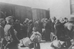 <p>Aleksander Belev, commissaire bulgare aux Affaires juives (au centre, avec un chapeau et face à l'objectif), supervise la déportation des Juifs. Skopje, Yougoslavie, mars 1943.</p>