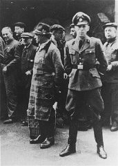 <p>An SS officer stands in front of Jews assembled for deportation. Vienna, Austria, 1941-1942.</p>