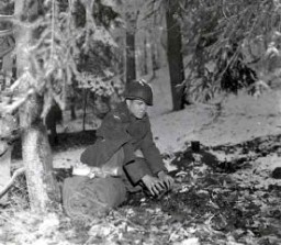 """<p>A soldier prepares to bed down for the night in a Belgian forest during the <a href=""""/narrative/8156/en"""">Battle of the Bulge</a>. December 21, 1944. <a href=""""/narrative/8129/en"""">US Army Signal Corps</a> photograph taken by J Malan Heslop.</p>"""