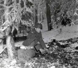 <p>Un soldat se prépare à passer la nuit dans une forêt belge au cours de la Bataille des Ardennes. 21 décembre 1944. Corps de transmission de l'Armée américaine, photographie prise par J. Malan Heslop.</p>