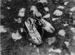 "<p>A pair of shoes left behind after a deportation action in the <a href=""/narrative/3182"">Kovno</a> ghetto. Photographer George Kadish captioned the photo ""The body is gone."" Kovno, Lithuania, circa 1943.</p>"