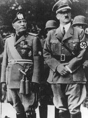 "<p>Benito Mussolini and <a href=""/narrative/43/en"">Adolf Hitler</a> stand together on an reviewing stand during a official visit to occupied Yugoslavia, 1941–43.</p>"