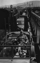 """<p>This photograph shows German vehicles that have been loaded on trains headed toward the <a href=""""/narrative/6718/en"""">eastern front</a> to reinforce German forces during the <a href=""""/narrative/2972/en"""">invasion of the Soviet Union</a> in 1941. A German soldier poses in the front car.</p>"""