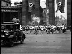 "<p>In 1933, Nazi Party leader Adolf Hitler became chancellor of Germany and quickly turned the nation's fragile democracy into a one-party dictatorship. Police rounded up thousands of political opponents, detaining them without trial in concentration camps. The Nazi regime also put into practice racial policies that aimed to ""purify"" and strengthen the Germanic ""Aryan"" population. A relentless campaign began to exclude Germany's one-half million Jews from all aspects of German life. For two weeks in August 1936, Adolf Hitler camouflaged his antisemitic and expansionist agenda while Berlin hosted the Summer Olympic Games. Hoping to impress the many foreign visitors who were in Germany for the games, Hitler authorized a brief relaxation in anti-Jewish activities (including even the removal of signs barring Jews from public places). The games were a resounding propaganda success for the Nazis. They presented foreign spectators with the image of a peaceful and tolerant Germany. Here, Hitler formally opens the 1936 Summer Olympic Games in Berlin. Inaugurating a new Olympic ritual, a lone runner arrived bearing a torch carried by relay from the site of the ancient Games in Olympia, Greece.</p>"