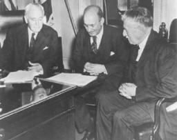 <p>Photo taken in Secretary of State Cordell Hull's office on the occasion of the third meeting of the War Refugee Board. Hull is at the left, Secretary of the Treasury Henry Morgenthau, Jr., is in the center, and Secretary of War Henry L. Stimson is at the right. Washington, DC, United States, March 21, 1944.</p>