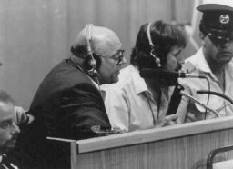 <p>Defendant John Demjanjuk comments on documents being viewed on a large screen in court. Jerusalem, Israel, July 27, 1987.</p>