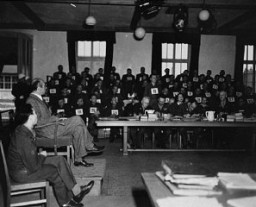 "<p>A witness testifies during the <a href=""/narrative/3880/en"">Mauthausen</a> concentration camp trial. The man standing in the background is defendant Willy Eckert, a member of the SS. The trial took place before an <a href=""/narrative/9935/en"">American Military Tribunal</a> in Dachau, Germany. March-May 1936. </p>"